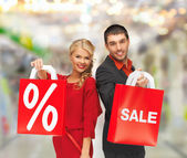 Smiling man and woman with shopping bag — Stock Photo