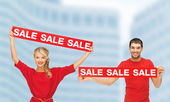 Woman and man with red sale signs — Stock Photo