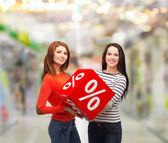 Two smiling teenage girl with percent sign on box — Stock Photo