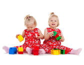 Two twin girls in red dresses playing with blocks — Stock Photo
