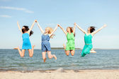 Smiling girls jumping on the beach — Stock Photo
