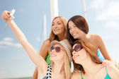 Smiling girls taking photo in cafe on the beach — Stock Photo