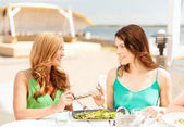 Smiling girls in cafe on the beach — Stock Photo