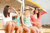 Usměvavá děvčata s drinky na pláži — Stock fotografie