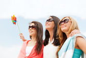 Smiling girls in shades having fun on the beach — Stock Photo