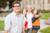 Teenage boy with classmates on the back — Stock Photo