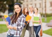 Tonårsflicka med mappar och kompisar på baksidan — Stockfoto