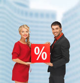 Smiling man and woman with percent sign — Stock Photo