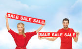 Smiling woman and man with red sale signs — Stock Photo