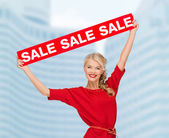 Smiling woman in dress with red sale sign — Stock Photo