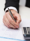 Close up of businessman with papers and calculator — Stock Photo