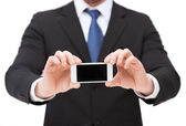 Businessman showing smartphone with blank screen — Stock Photo