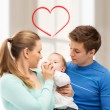 Family and adorable baby with feeding-bottle — Stock Photo