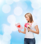 Smiling girl with postcard and bouquet of flowers — Stock Photo