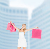 Woman with shopping bags in dress — Stock Photo