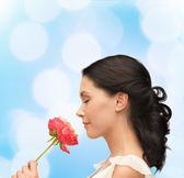 Smiling woman smelling flower — Stock Photo