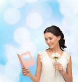 Young woman holding flower and postcard — Stock Photo