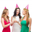 Three women in pink hats with champagne glasses — Stock Photo