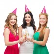 Three women in pink hats with champagne glasses — Stock fotografie #38741239