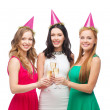 Three women in pink hats with champagne glasses — Stock Photo #38741239