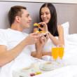Smiling couple having breakfast in bed in hotel — Stock Photo