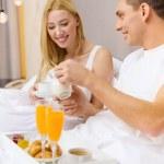 Smiling couple having breakfast in bed in hotel — Stock fotografie