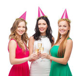 Three women in pink hats with champagne glasses — Foto Stock