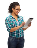 Smiling black student in eyeglasses with tablet pc — Stock Photo