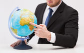 Businessman pointing finger to earth globe — Stock Photo