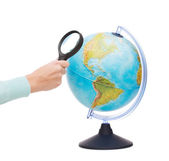 Woman hand holding magnifying glass over globe — Stock Photo