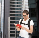 Student in eyeglasses with backpack and book — Stock Photo