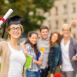 Smiling teenage girl in corner-cap with diploma — Stock Photo #38805797