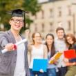 Smiling teenage boy in corner-cap with diploma — Stock Photo