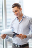 Smiling businessman with clipboard in office — Stok fotoğraf