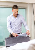 Businessman packing things in suitcase — Stock Photo