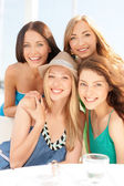 Group of smiling girls in cafe on the beach — Stock fotografie