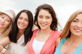 Group of smiling girls chilling on the beach — Stock Photo