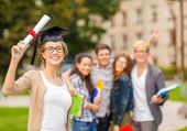 Smiling teenage girl in corner-cap with diploma — Stock Photo