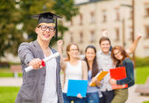 Smiling teenage boy in corner-cap with diploma — Stock Photo