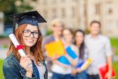Usmívající se dospívající dívka v rohu čepice s diplomem — Stock fotografie