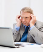 Upset older businessman with laptop in office — Stock Photo