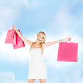 Woman with shopping bags in dress and high heels — Stock Photo