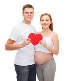 Happy young family expecting child with big heart — Stock Photo