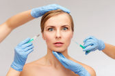 Woman face and beautician hands with syringe — Stock Photo