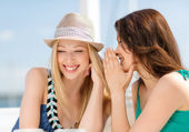 Girls gossiping in cafe on the beach — Stock Photo