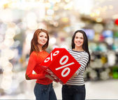 Two smiling teenage girl with percent sign on box — Foto de Stock