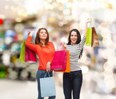 Two smiling teenage girls with shopping bags — Stock Photo