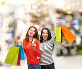 Teenage girls with shopping bags and credit card — Stock Photo