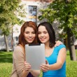 Stock Photo: Two smiling teenagers with tablet pc computer
