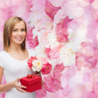 Smiling woman with bouquet of flowers and gift box — Stock Photo #39203743